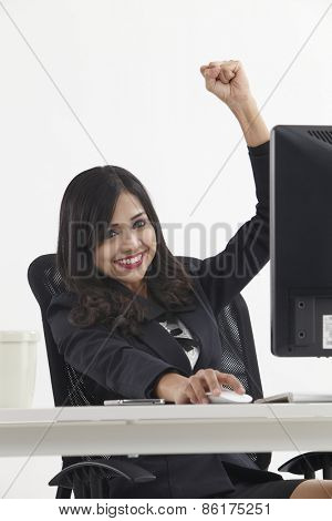 business woman sitting in front monitor cheering