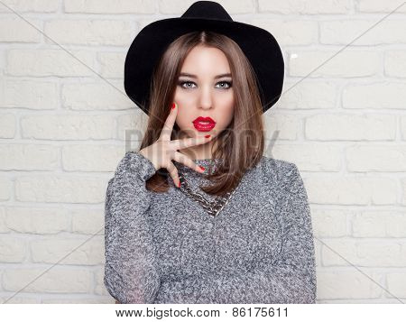 beautiful sexy young girl in a black hat with red full lips, bright makeup and painted my nails red