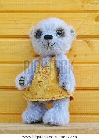 Teddybär Chupa vor einer Holzwand