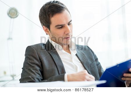 Successful  Young Businessman Reading A Report