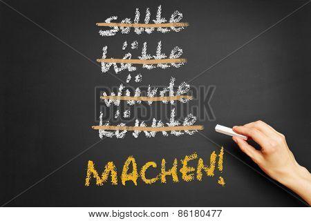 Hand writing motivational slogan in German (Do It) on a chalkboard