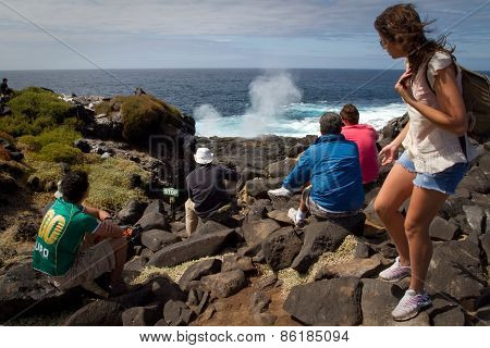 Tourists overlooking sea geyser in Espanola Island, Galapagos