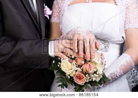 Hands Of The Newlyweds With Wedding Bouquet
