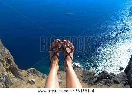 Woman sitting at the top with her legs over the sea surface of nice blue colour