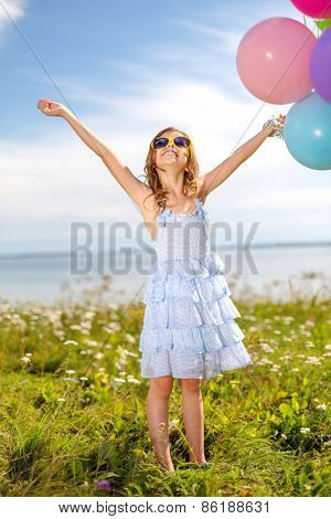 summer holidays, celebration, children and people concept - happy girl waving hands with colorful balloons outdoors