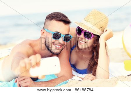 A picture of a happy couple taking selfie at the beach