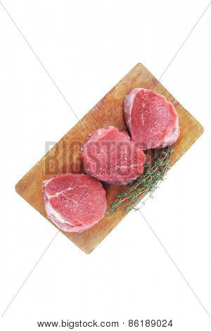 raw red meat : three fresh beef fillet chops with thyme twig on wooden plate . isolated over white background