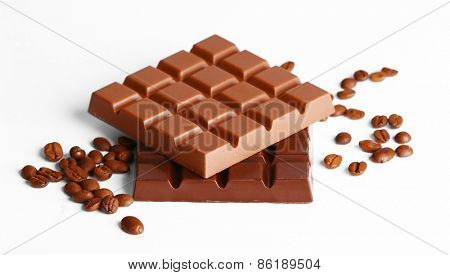 Milk and black chocolate bars with coffee beans isolated on white