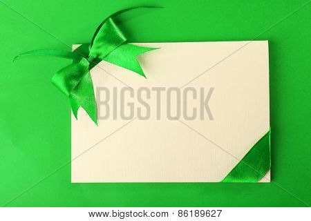 Card decorated with bow on green background