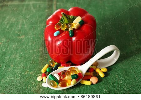 Pepper and colorful pills, on wooden background