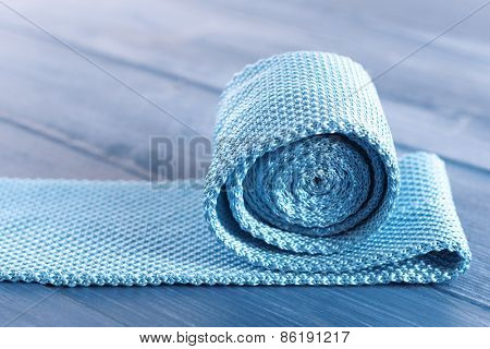 Blue male tie on color wooden table background