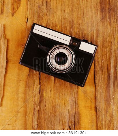 Retro photo camera on wooden background