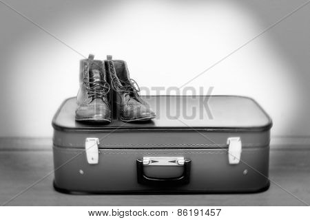 Vintage suitcase with male shoes on floor in shades of grey