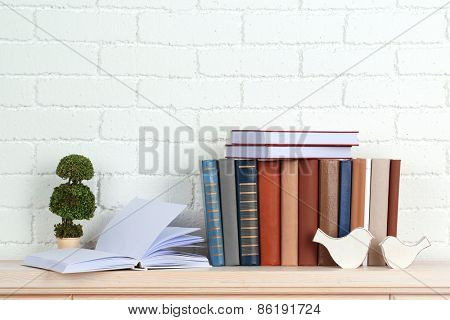 Books on shelf on wall background