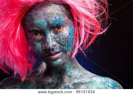 Woman with pink wig hair. Creative portrait with face art and body art.