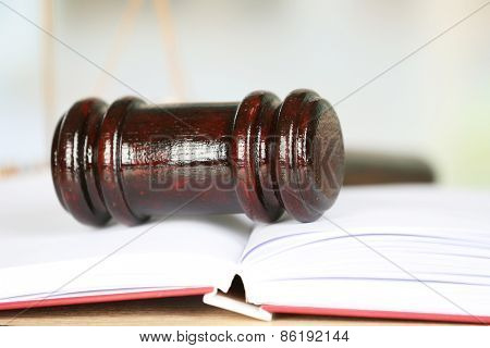 Wooden judges gavel lying on law book, close up