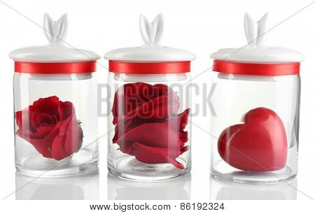 Rose flower, petals and decorative heart in glass jars  isolated on white