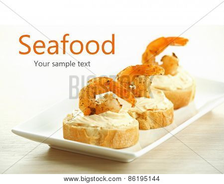 Appetizer canape with shrimp on plate on table close up
