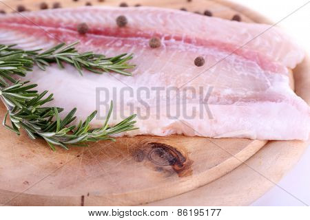 Pangasius fillet on wooden cutting board on white background