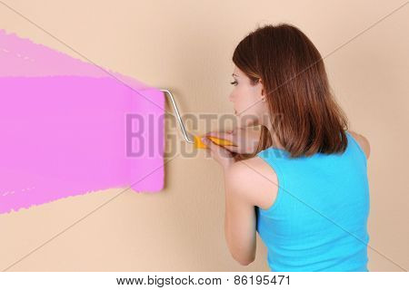 Beautiful girl paints wall in room