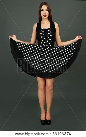Beautiful young woman in dots dress on dark gray background