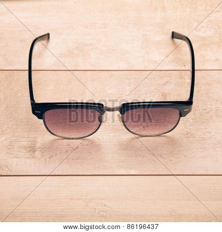 black sunglasses on wood floor