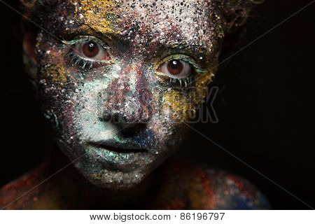 Portrait of woman with unusual paint make-up on black background