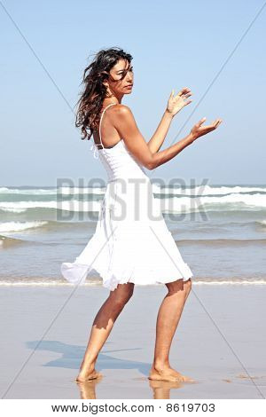 Young attractive woman dancing at the beach