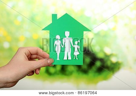 Cutout house with paper family in female hand on bright blurred background