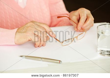 Hands of adult woman with pen, glasses and glass of water on table, on dark background