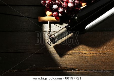Glass bottle of wine with corkscrew and grapes in dark with light on wooden table background