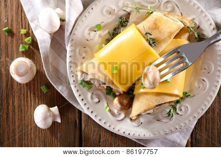 Pancakes with creamy mushrooms in plate on wooden table, top view