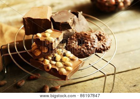 Still life with set of chocolate with nuts on metal stand, closeup