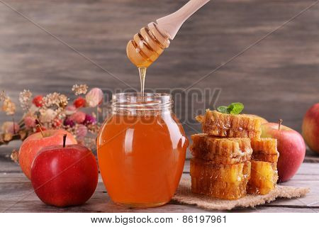 Delicious honey with apple on table on wooden background