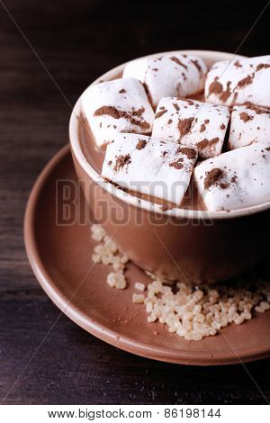Cup of cocoa with marshmallows on wooden table, closeup