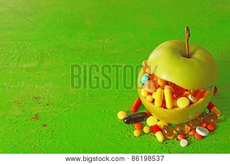 Apple and colorful pills, on color wooden background