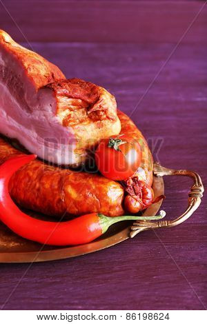 Assortment of smoked meat on metal tray on color wooden table background