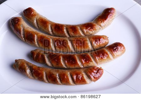 Grilled sausages on plate close up