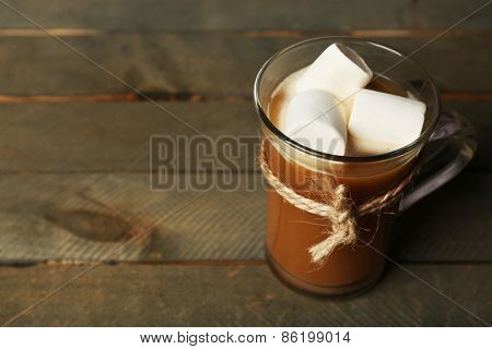 Glass cup of cocoa with marshmallows on rustic wooden planks background