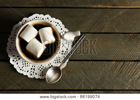 Cup of coffee with marshmallows on rustic wooden planks background