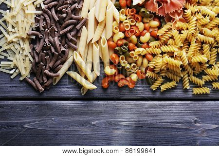 Different types of pasta on wooden planks background