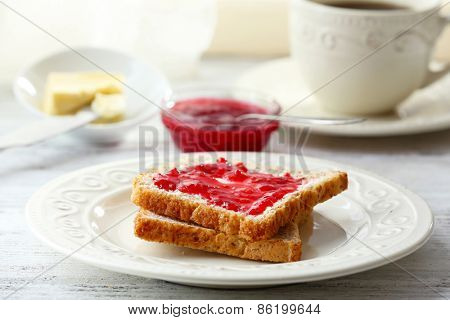 Toasts with jam on plate with cup of tea on light background