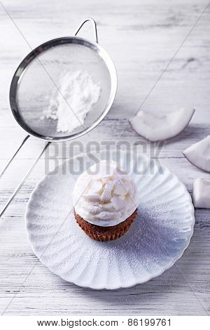 Delicious coconut cupcake with cream on color wooden table background