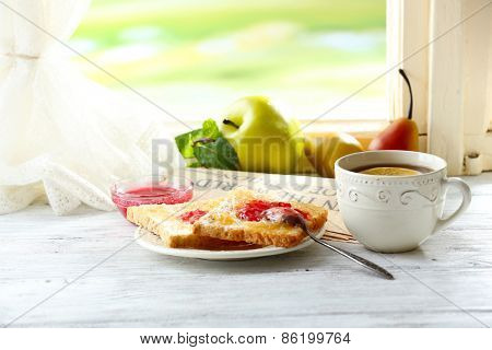 Toasts with jam on plate and cup of tea on bright background