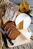 picture of brie cheese  - Black bread brie cheese knife and honey on a cutting board - JPG