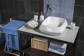 picture of bathroom sink  - detail of a modern bathroom with sink and accessories bathroom cabinet and blue bathroom tiles - JPG