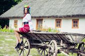 foto of wooden horse  - beautiful young woman wearing national ukrainian clothes sitting on old horse drawn wooden cart - JPG