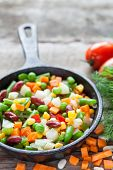 picture of lenten  - Mixed vegetable meal in old black frying pan closeup and ingredients on wooden rustic table - JPG