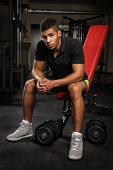stock photo of sitting a bench  - young man sitting on bench at gym - JPG