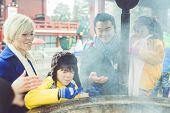 foto of shogun  - family breathing purification smoke in sensoji temple - JPG